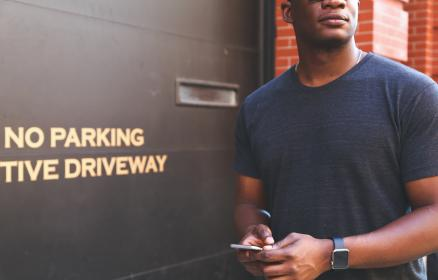 guy, man, people, african american, hands, texting, smartphone, cell phone, mobile, apple watch, no parking, garage, city, bricks, urban