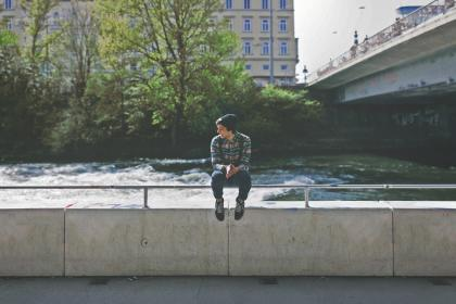 boy, kid, guy, teenager, hat, sitting, water, bridge, tree, city, building, ledge, smile, knapsack, backpack, shoes, jeans, concrete, student