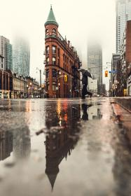 architecture, building, infrastructure, skyscraper, tower, city, urban, skyline, landmark, road, street, raining, water, reflection, people, walking, umbrella, traffic, light, pedestrian, crossing