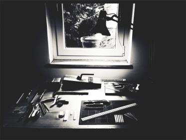 tools, supplies, materials, pliers, razor blades, xacto knife, knives, screw driver, desk, window, lamp, black and white, workshop