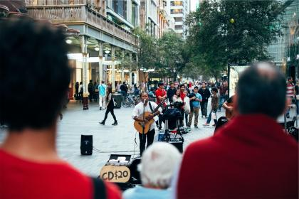 street performer, busker, musician, music, instrument, guitar, singing, singer, crowd, spectators, people, stores, shops, audience, speakers