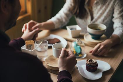 people, man, woman, couple, holding hands, dinner, date, restaurant, coffeehouse, shop, cupcakes, food, eating, desserts, coffee, drink, dining, table