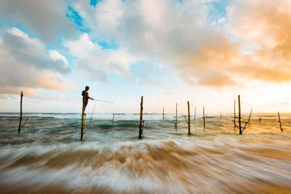 nature, landscape, water, ocean, sea, waves, splash, wood, stilts, sticks, person, people, stand, fish, sky, clouds,horizon