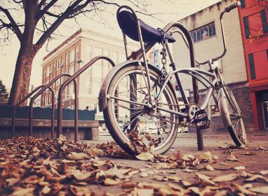 bike, bicycle, hanldebars, chain, leaves, pavement, concrete, railing, buildings