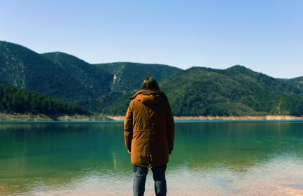 guy, man, male, people, back, contemplate, style, hood, coat, view, water, lake, surface, still, calm, coast, shore, mountains, lush, vegetation, sky, picturesque