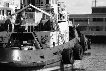 fishing boat, ship, pier, dock, port, harbor, harbour, tires, ladders, steps, ropes, equipment, black and white