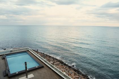 swimming pool, wood, deck, railing, rocks, coast, water, sea, ocean, sky, clouds