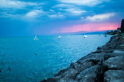 sunset, sailboats, lake, water, rocks, coast, horizon, sky, clouds, storm, cloudy, landscape,  nature, blue