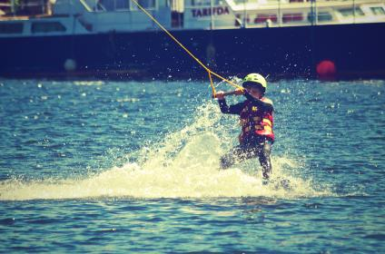 waterskiing, boy, child, kid, rope, life jacket, helmet, boat, splash