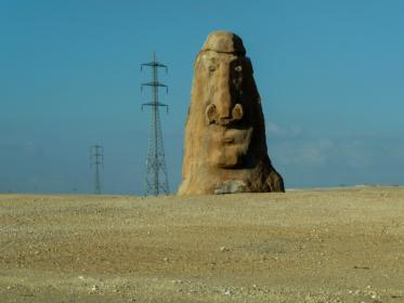 carved stone, rock, face, power lines, ground