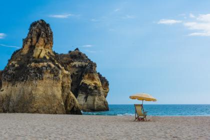 beach, sand, water, ocean, sea, lounge chair, umbrella, rocks, cliffs, coast, sky, sunshine, summer