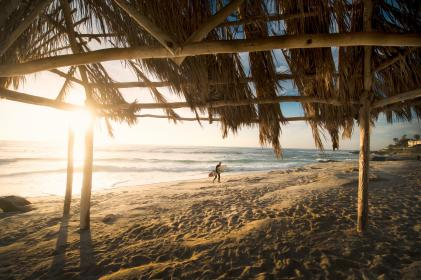 nature, beach, shore, sand, hut, nipa, straw, roof, wood, posts, water, ocean, sky, clouds, horizon, person, surf, light, shadow, dusk, dawn
