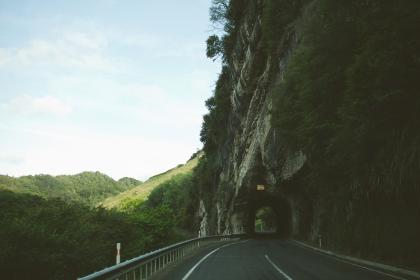 sky, road, tunnel, winding, hills, grass, trees, mountains, rocks. cliffs, driving