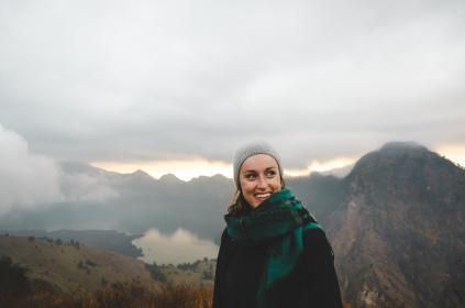 people, woman, happy, scarf, mountaineer, bonnet, mountain, travel, adventure, trek, hike, clouds, sky, fog, lake, trees, green, grass
