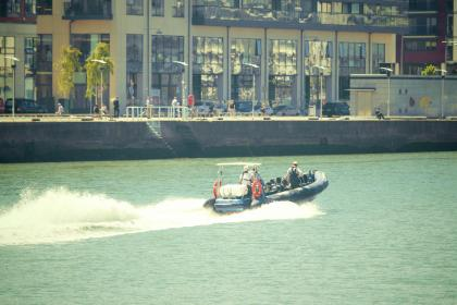 speedboat, water, waves, buildings, city, urban, people, walking, pedestrians, boardwalk