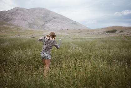 woman, girl, lady, people, back, walk, path, style, grasslands, wild, grass, mountains, slope, sky, clouds, horizon, travel