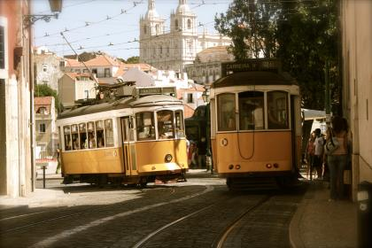 cable cars, transportation, street, road, cobblestone, sidewalk, city, buildings, passengers, people, pedestrians