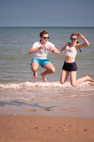 people, jumping, beach, boy, girl, fun, play, ocean, water, sea, shore, coast, sand, vacation, happy, young, leisure, summer