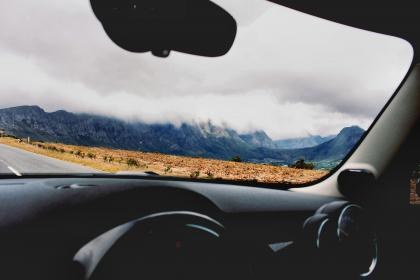 car, vehicle, travel, transportation, steering wheel, nature, mountain, adventure, fog, clouds, sky, hike, climb, grass, road, plants
