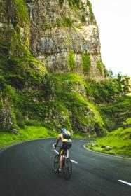 cyclist, bike, bicycle, racing, road, street, pavement, fitness, exercise, guy, man, people, backpack, mountains, cliffs, green, grass, sports