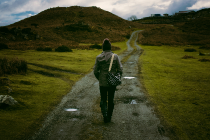 woman,  walking,  track,  mountain,  hill,  green,  grass,  spotted,  bag,  black,  hat,  trail,  path,  clouds,  sky,  blue