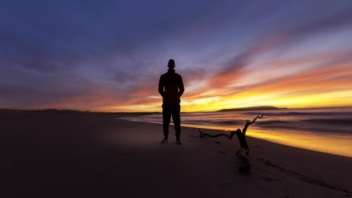 guy, man, male, people, stand, nature, sky, clouds, fiery, horizon, dusk, dawn, light, shadows, silhouette, travel, trek, beach, shore, sand, tree, stump, gradient, orange, yellow, purple, blue