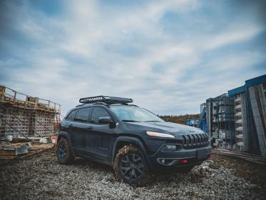 car, vehicle, wheels, bumper, construction, architecture, rocks, structure, sky, clouds, mud, woods, steel