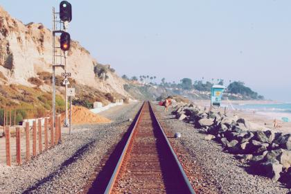 train tracks, pebbles, rocks, sand, beach, water, sky, red light, green light, sunny, summer, railroad, railway, transportation