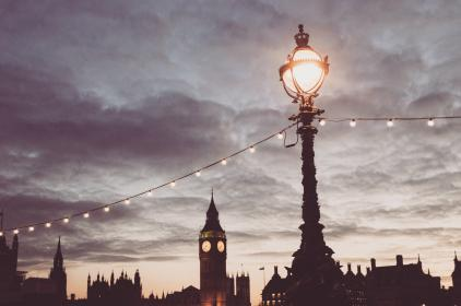sky, clouds, lamp post, lights, string lights, clock, city, urban, night, dark, evening, silhouette, shadows, cityscape, buildings, architecture