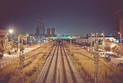 night, dark, train tracks, railroad, railway, buildings, industrial, power lines, cars, vans, street lights, lamp posts