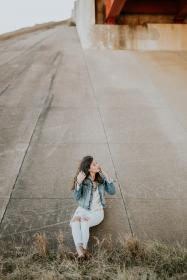 people, girl, woman, beauty, model, road, highway, fashion. clothing, outdoor, adventure, concrete, sitting, ripped, jeans, denim