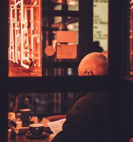 people, man, old, back, cup, coffee, cafe, restaurant, establishment, table, glass, wooden, paper, reading, sitting, signage