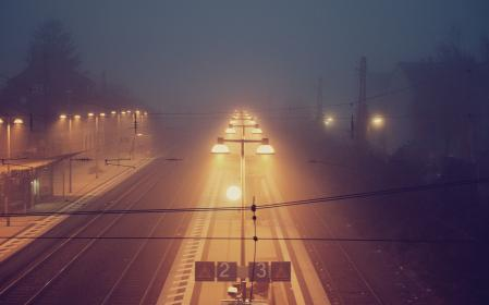 night, dark, lights, mist, fog, train tracks, railroad, railway, signs, lamp posts, evening