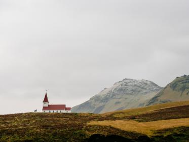 church, cross, red, roof, grey, sky, mountains, cliffs, hills, fields, valleys, grass, dirt, outdoors, plains, flag