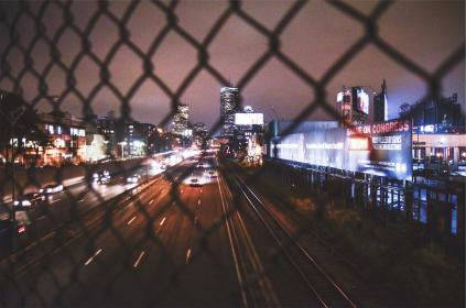 overpass, highway, road, chainlink, fence, billboards, night, dark, evening, cars, lights, buildings, city