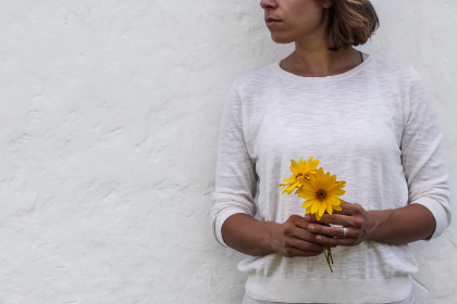 woman,  holding,  flower,  wall,  background,  copy space,  lady,  girl,  feminine,  beautiful,  elegant,  floral,  blossom,  bloom,  texture,  white wall,  yellow,  adult,  bouquet,  person,  pretty,  spring,  summer