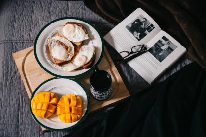 food, mangoes, fruit, dessert, egg, pastry, book, read, eyeglasses, article, tray, cup, mug, bread