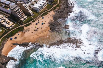sea, ocean, water, coast, rocks, beach, shore, aerial, view, buildings, structure, resort, cottage, vacation, travel