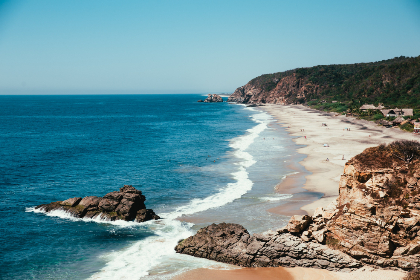 beach,  ocean,  shore,  shoreline,  sand,  rocks,  nature,  outdoors,  outside,  sunny,  water,  wet,  sky,  mountains,  people,  relaxing,  waves,  scenic,  vacation,  swimming