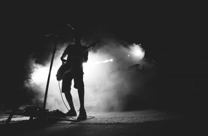 guy, man, male, people, stand, light, shadow, silhouette, spotlight, lighting, smoke, stage, mic, microphone, music, musician, play, event, concert, black and white, still, bokeh