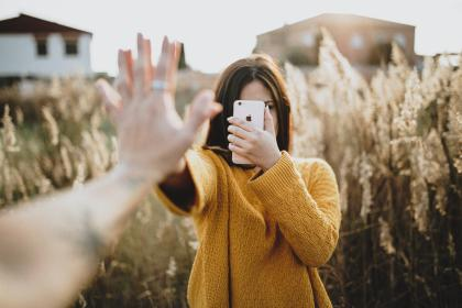 people, woman, couple, ring, hands, yellow, sweater, field, house, iphone, cellphone, phone