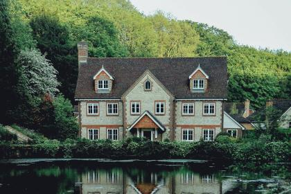 house, home, mansion, residence, neighborhood, neighbors, windows, doors, nature, water, pond, lake, reflection, trees, plants, bushes, vines, sky
