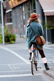 girl, woman, cyclist, bike, bicycle, street, road, intersection, crosswalk, city, urban, bag, hat, people