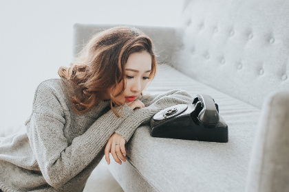 alone,  girl,  young,  lady,  phone,  wait,  waiting,  portrait,  sad,  sexy,  person,  people,  woman,  beauty,  asian, call, couch, sofa