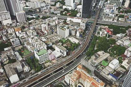 architecture, building, infrastructure, aerial, view, road, street, car, vehicle, city, tower, skyline, rooftops, green, trees, plants, nature