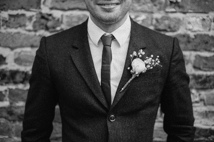 groom, close-up, suit, black & white, wedding, wedding day, tie, happy, love, romantic, brick, brick wall