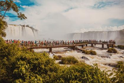 people, crowd, travel, bridge, river, water, rocks, green, grass, nature, plant, tree, waterfalls, cloud, sky, tourist spot