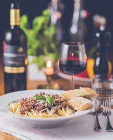 pasta, food, bread, breakfast, lunch, dinner, plate, spoon, fork, tableware, wine, glass, bottle, drink, candle, date, cloth, table, setup, restaurant