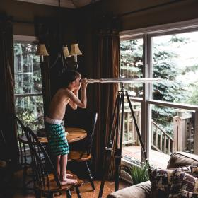 people, man, boy, kid, guy, telescope, indoor, house, interior, chair, table, living, room, window, glass