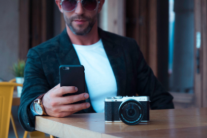 man,  camera,  mobile,  phone,  technology,  pose,  sunglasses,  table,  bar,  watch,  wait,  dslr,  photography,  photographer,  device,  telephone